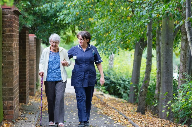 Caregiver Walking with Elderly Patient